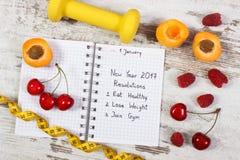 Nieuwe die jaarresoluties in notitieboekje worden geschreven over oude raad stock foto's