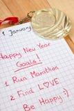 Nieuwe die jarenresoluties in notitieboekje en gouden medaille worden geschreven Stock Foto's