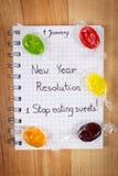 Nieuwe die jarenresoluties in notitieboekje en kleurrijk suikergoed worden geschreven Stock Foto