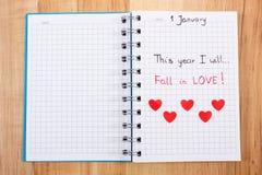 Nieuwe die jarenresoluties in notitieboekje en rode document harten worden geschreven Stock Foto