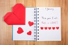 Nieuwe die jarenresoluties in notitieboekje en rode document harten worden geschreven Stock Fotografie