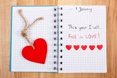 Nieuwe die jarenresoluties in notitieboekje, rode houten en document harten worden geschreven Stock Foto's