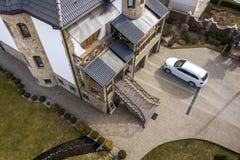 Nieuwe dure witte die auto in bedekte well-kept yard met groen gazon, decoratieve struiken en baksteenomheining wordt geparkeerd  stock afbeeldingen