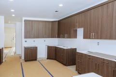 Nieuwe geïnstalleerde houten keukenkasten met modern decoratief roestvrij staal stock afbeelding