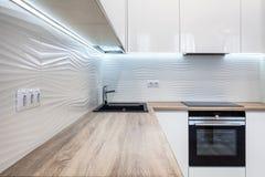 Nieuwe heldere moderne keuken met gebouwd in oven en chroomwaterkraan en een houten lijstbovenkant stock foto