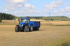 Nieuwe Holland Tractor en Blauwe Aanhangwagen Autumn Field Landscape royalty-vrije stock foto