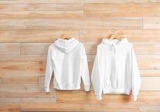 Nieuwe hoodiesweaters met hangers op houten muur stock afbeelding