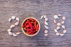Nieuwe jaar 2018 droge knoflook en Spaanse pepers gezet op oude houten achtergrond Royalty-vrije Stock Afbeelding
