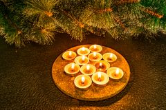 Nieuwe jaar en Kerstmis, groene kunstmatige pijnboom op een zwarte achtergrond in het licht van kaarsen Gele warme eenvoudige aan royalty-vrije stock foto
