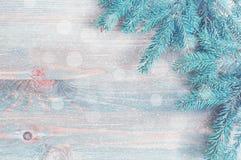 Nieuwe jaar en Kerstmisachtergrond Blauwe sparrentakken met sneeuwvlokken op de lichte houten achtergrond stock afbeelding