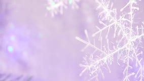 Nieuwe jaar en van de chrismasboom decoratie in een vorm van een sneeuwvlok met lichtpaars backgroungonduidelijk beeld stock videobeelden