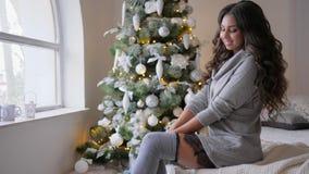 Nieuwe jaar` s vooravond, brunette met krullen in een warme kleding en lange sokken op bed dichtbij de Kerstmisboom stock videobeelden