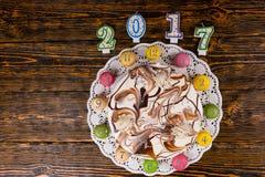 Nieuwe jaarcake en macarons als klok dichtbij kaarsen nummer 2017 o Stock Afbeeldingen