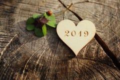 Nieuwe jaargroeten met een houten hart, een gelukkige klaver en een onzelieveheersbeestje stock afbeeldingen