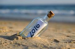 2016, Nieuwe jaarpartij, fles met bericht op het strand Stock Foto's