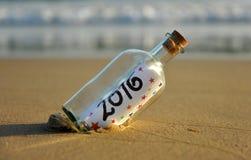 2016, Nieuwe jaarpartij, fles met bericht op het zand Stock Afbeelding