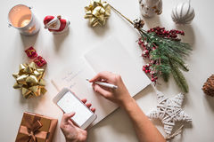 Nieuwe jaarresoluties die met een hand worden geschreven over notitieboekje met nieuwe jarendeco Stock Fotografie