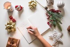 Nieuwe jaarresoluties die met een hand worden geschreven over notitieboekje met nieuwe jarendeco Stock Foto's