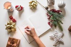Nieuwe jaarresoluties die met een hand worden geschreven over notitieboekje met nieuwe jarendeco Stock Afbeeldingen