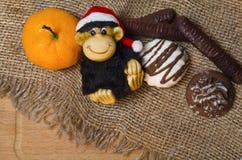 Nieuwe jaarsamenstelling met een aap, een mandarijn en koekjes Stock Afbeeldingen