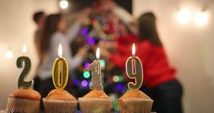 Nieuwe jaarviering Cupcakes met kaarsen in nummer 2019 tribune op de lijst vóór het vrolijke bedrijf Nieuw vieren stock video