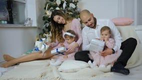 Nieuwe jarenvooravond, ouders met dochters open giften thuis op achtergrond van verlichte Kerstmisboom stock video