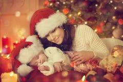 Nieuwe Kerstmis Pasgeboren Baby en Moeder, - geboren Jong geitjeslaap met Mamma stock fotografie