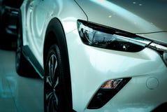 Nieuwe luxe witte die auto in moderne toonzaal wordt geparkeerd Het bureau van het autohandel drijven Elektrisch of hybride autot stock fotografie