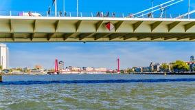 Nieuwe Maas rzeka z czerwonym kablem zostawał Willems most w tle przeglądać spod Erasmus mostu w Rotterdam fotografia stock