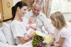 Nieuwe moeder met baby en familie in het ziekenhuissmilin stock afbeelding