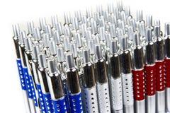Nieuwe pennen in houder in rijen op witte achtergrond stock foto's