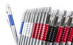 Nieuwe pennen in houder in rijen op witte achtergrond stock afbeeldingen