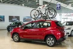 Nieuwe rode familieauto Peugeot 2008 met een onderstel op het dak voor fietsen in het autohandel drijven stock afbeeldingen