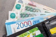 Nieuwe Russische bankbiljetten in benamingen van 1000, 2000 en 5000 roebels en creditcards in een zwart close-up van de leerbeurs Stock Foto