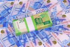 Nieuwe Russische roebels: een pak twee-roebel bankbiljetten in een Bankpakket op de achtergrond van twee duizend rekeningen stock fotografie