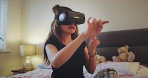 Nieuwe technologie die door een tienermeisje onderzoeken in haar slaapkamer, die een VR gebruiken zij wat betreft virtueel het pr stock video