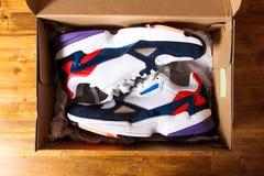 Nieuwe tennisschoenen in de doos op houten achtergrond royalty-vrije stock fotografie