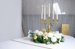 Nieuwe Year& x27; s de decoratie en een gouden kandelaar met het branden van kaarsen bevinden zich op de oppervlakte van een witt royalty-vrije stock foto's