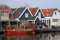 Dutch houses and boat on river Vecht in Holland. Colorful houses in Nieuwersluis on the river Vecht in the Netherlands Stock Photography