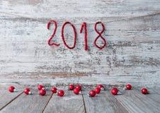Nieuwjaar 2018 achtergrond op een houten oppervlakte met glanzende aantallen Stock Afbeelding