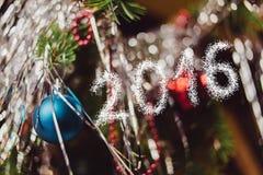 Nieuwjaar 2016 over glanzende achtergrond met Kerstmisdecoratie Stock Afbeeldingen