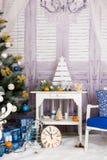 Nieuwjaar` s binnenlandse ruimte De kerstboom met kleurrijke ballons wordt verfraaid en de giften liggen op de vloer die Kerstmis Royalty-vrije Stock Foto's