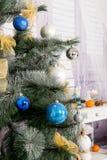 Nieuwjaar` s binnenlandse ruimte De kerstboom met kleurrijke ballons wordt verfraaid en de giften liggen op de vloer die Kerstmis Royalty-vrije Stock Afbeeldingen