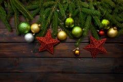 Nieuwjaar` s greens, gele en zilveren ballen samen met rode sterren en met levende spartakken op een houten achtergrond Hoogste m Stock Foto's