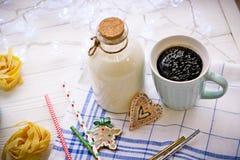 Nieuwjaar` s stilleven met een fles, een kop, koekjes, deegwaren stock afbeeldingen