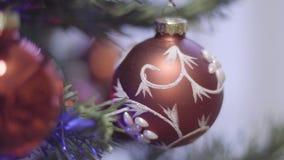 Nieuwjaar` s stuk speelgoed die op een van het takkerstmis en Nieuwjaar Decoratie slingeren Samenvatting Vage Bokeh-Vakantieachte stock videobeelden