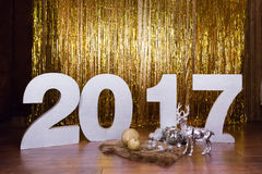 2017 nieuwjaar ` s tegen een gouden klatergoudachtergrond Stock Afbeelding