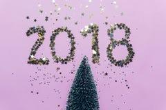 Nieuwjaar 2018 schrijven samengesteld uit schitterende confettien over Kerstboom Stock Afbeelding