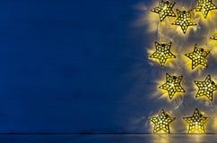 Nieuwjaarachtergrond - de lichtensterren branden op donkerblauwe houten muur met lege plank Royalty-vrije Stock Fotografie