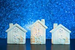 Nieuwjaarachtergrond met witte plattelandshuisjes in de sneeuw Brengt op Vaag Blauw onder schitteren lichtenachtergrond het conce royalty-vrije stock foto's